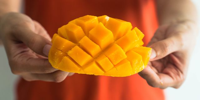 a young woman is holding a freshly sliced ripe mango
