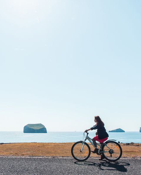 a young woman is riding bicycle by the shore