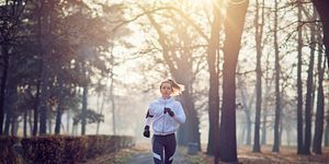 Young woman is running in the cold foggy morning