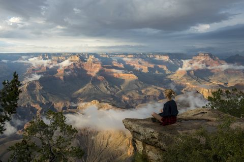 A young woman is sitting on a rock near Yavapai Point on the...