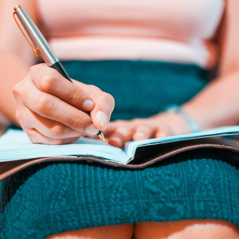 A young woman is writing on her journal while sitting on a couch