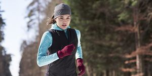 Young woman jogging in winter forest