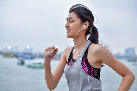 young woman jogging on footpath while listening music in city