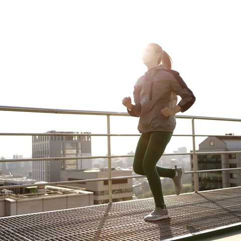 young woman jogging on rooftop