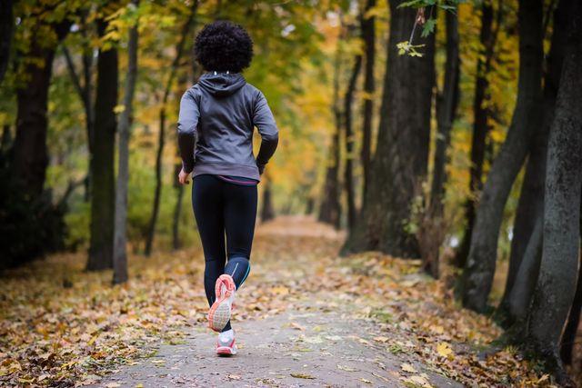 young woman jogging through the fall park, rear shot