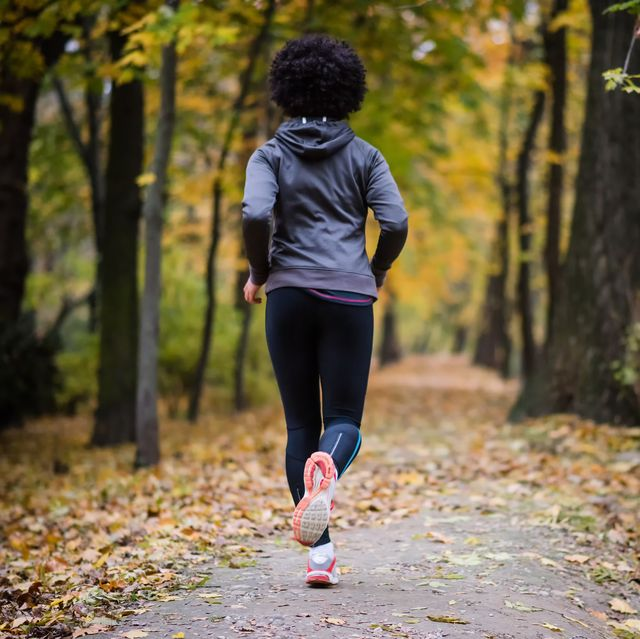 young woman jogging through the fall park