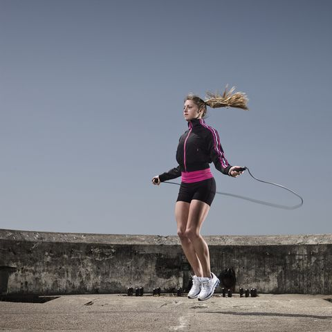 young woman jumping rope outdoors
