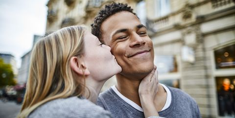 young woman kissing boyfriend in the city