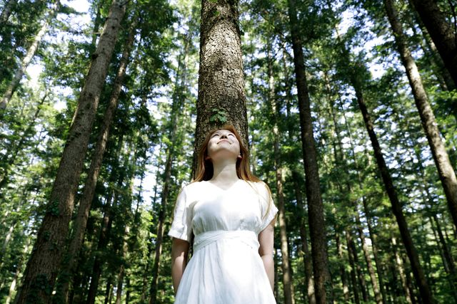 young woman leaning against tree in forest