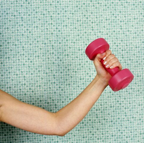 young woman lifting dumbbell, against tiled wall, close up