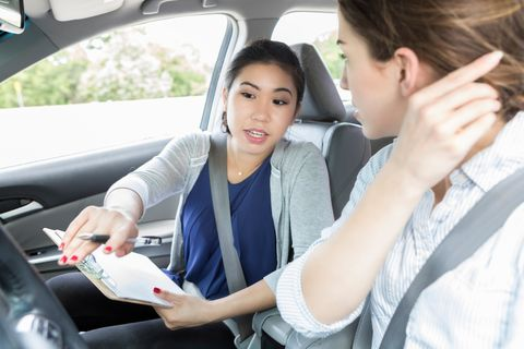 Young woman listens to instructions before driving test