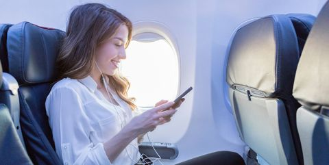 Young woman listens to music during air travel