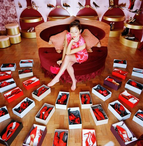Young woman looking at boxes of red shoes on shop floor, elevated view