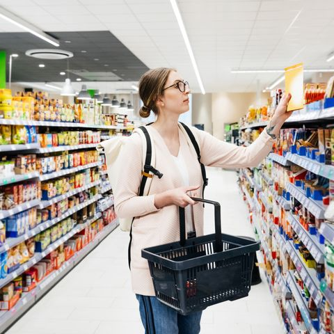 Young Woman Looking At Food Items While Grocery Shopping