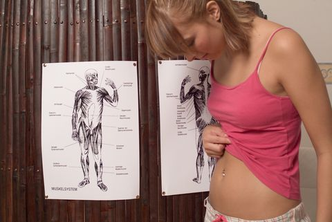 young woman looking at her stomach