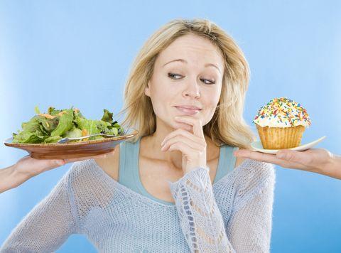 young woman looking at salad and cupcake, hand on chin, close up