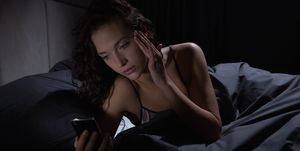 Young woman looking at smartphone in bed