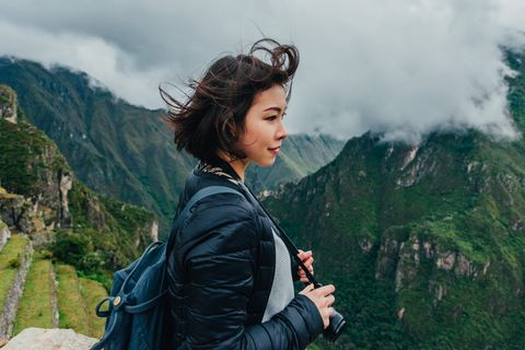 young woman looking at view from machu picchu in peru