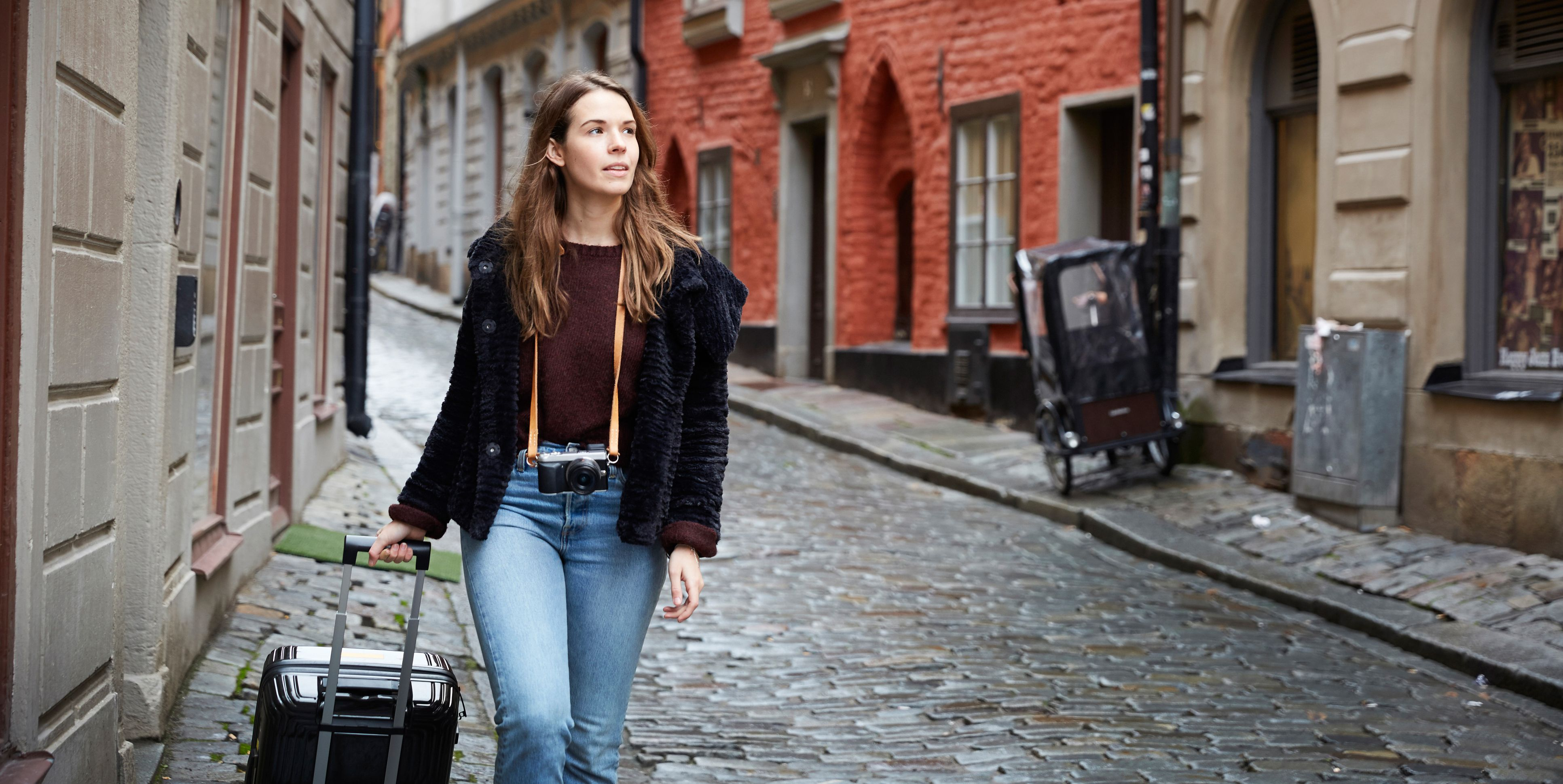 Young woman looking away while walking with luggage in alley
