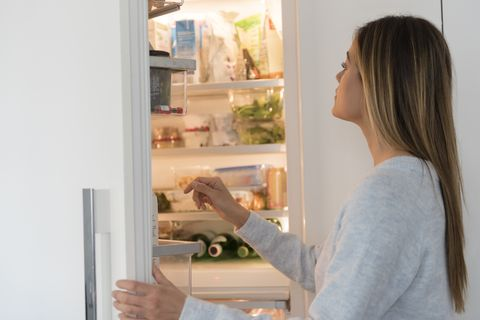 Young woman looking into refrigerator