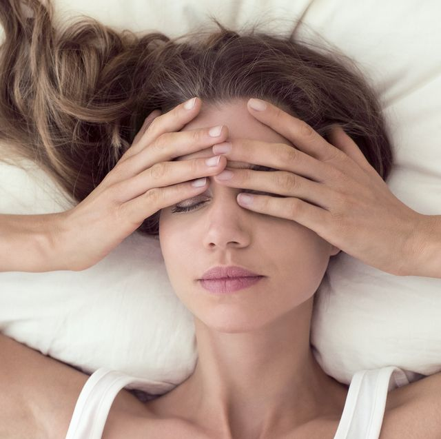 young woman lying in bed and covering eyes