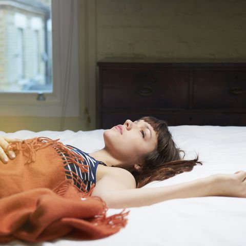 Young woman lying in bed with blanket