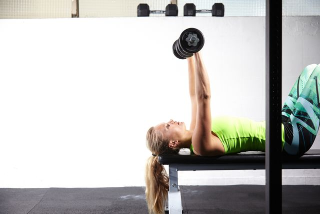young woman lying on training bench lifting bar bell in gym
