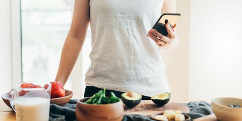 young woman making healthy smoothie for breakfast