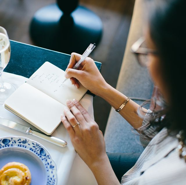 Young woman making notes whilst having champagne breakfast at boutique hotel in Italy