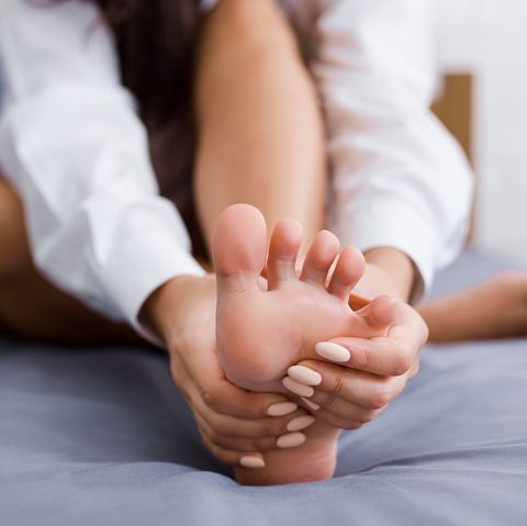 young woman massaging her foot on bed