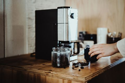 young woman measuring and pouring roasted coffee beans into coffee machine and preparing coffee at home in the early morning