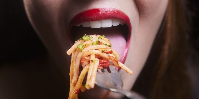 young woman mouth eating spaghetti pasta bolognese on a silver fork