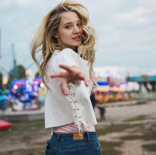 young woman on a funfair reaching out her hand