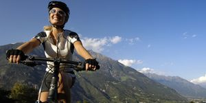 Young woman on a mountain bike under blue sky, Val Venosta, South Tyrol, Italy, Europe