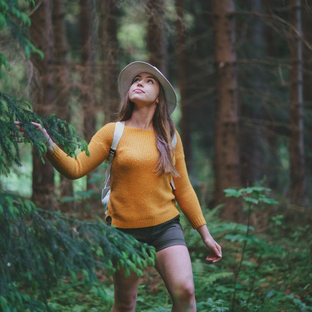 young woman on a walk outdoors in forest in summer nature, walking