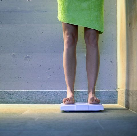 young woman on bathroom scales, low section