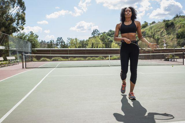 corredora con una raqueta en mano en una pista de tenis