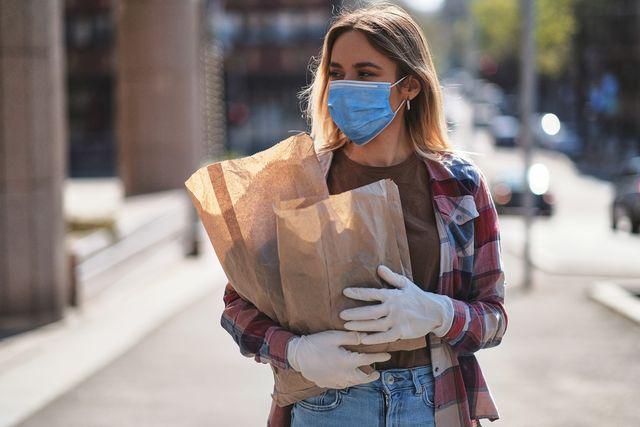 mujer con mascarilla saliendo de la compra