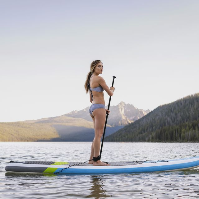 young woman paddle boarding on mountain lake