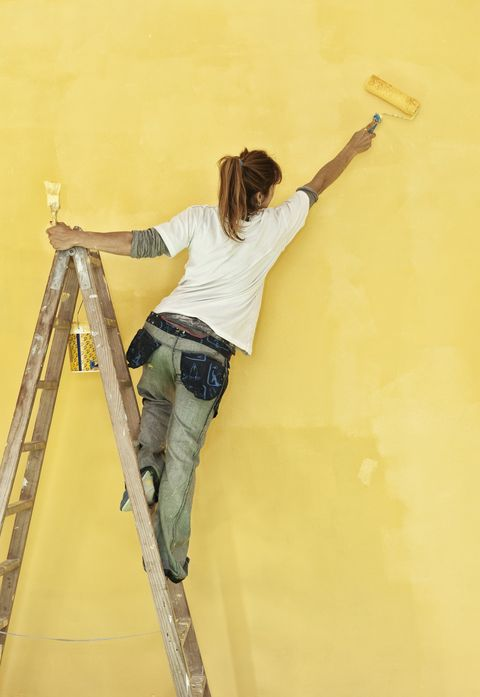 Young woman painting wall with yellow paint