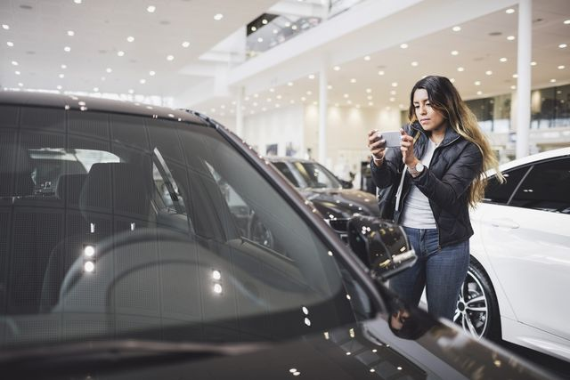young woman photographing new car through mobile phone at showroom