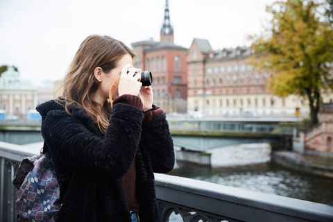 Young woman photographing through camera while standing on bridge in city