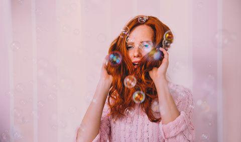 Mujer pelirroja con pelo rodeado de burbujas
