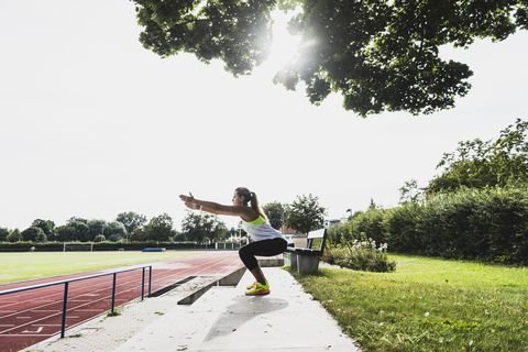 Young woman practicing in a track and field stadium