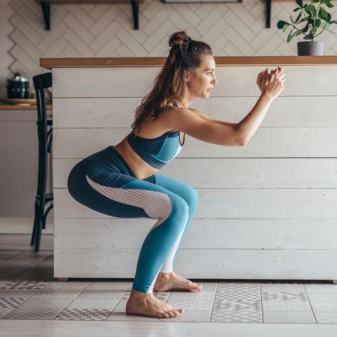 young woman practicing squats woman exercising at home