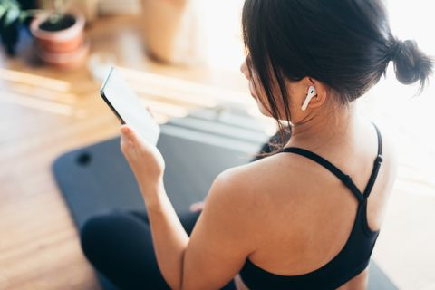 young woman practicing yoga and using smartphone at home