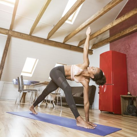 young woman practicing yoga in attic