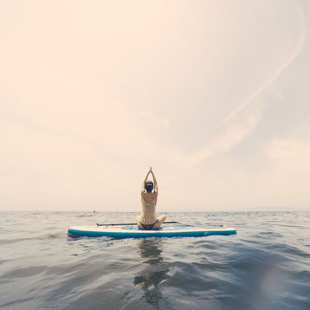 young woman practicing yoga on a paddleboard in the ocean