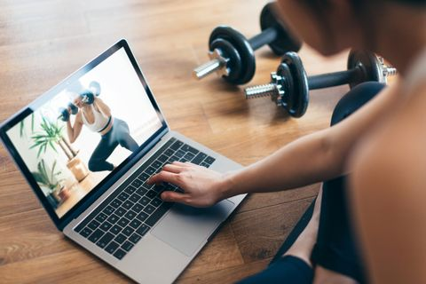 young woman practising weight training workout with a video lesson on laptop