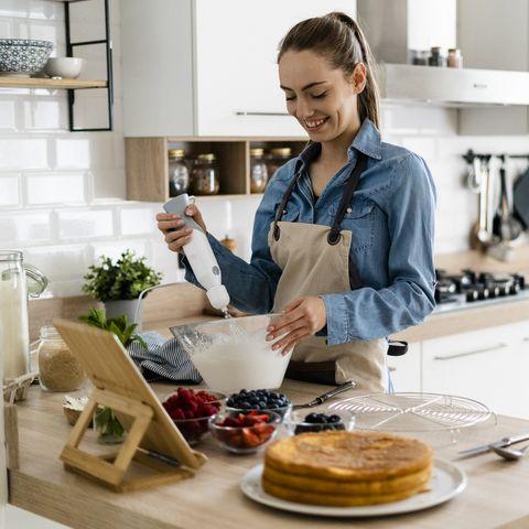 chica joven haciendo un pastel con batidora de mano